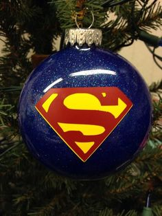 """Designed by Bri's Crafts & Things, these fun holiday ornaments are thin, round bulbs filled with lots of sparkle and vinyled with your favorite superhero! Ornaments measure about 3"""" in diameter and 1"""""""