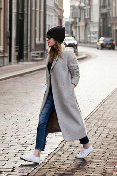 Layered winter outfit ideas - click and prepare for a stylish season. This combo (cropped jeans, a long coat, a beanie, and white sneakers) is so simple but SO good.