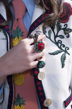 A closeup of the snake embroidered Gucci Spring Summer 2016 suit and bejeweled rings.