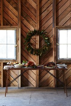 The Nordt family of Charles City, Virginia, host their Thanksgiving feast in the barn.In lieu of chairs, theyarrange bales of hay and drape them with handwoven blankets. The main table is set with small candles and antique 1920s Theodore Haviland china, in addition to the leaf-threaded wreath that hangs on the wall.