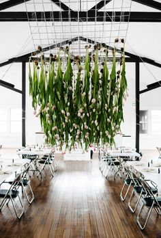Decorating your wedding on a budget? Buy flowers that are in season and hang them at your reception!