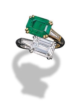 A TWIN-STONE EMERALD AND DIAMOND RING, BY MAUBOUSSIN  Of crossover design, set with a rectangular-cut emerald weighing 2.06 carats and a diamond weighing 2.10 carats to the tapered baguette-cut diamond shoulders and two-coloured hoop, mounted in platinum and 18K gold, with French assay marks
