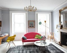 A yellow shell chair adds a fun color pop against the pink sofa.