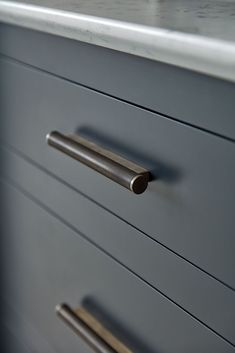The dark grey Nightshade paint colour is paired with bronze handles and Silestone Lyra work surface.