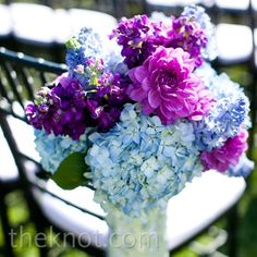 A mixture of cool blue and warmer purple flowers lined the ceremony aisles. But w blues and greens