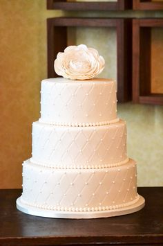 Ivory Quilted Beaded wedding cake, with a handmade Ranunculas sugar flower