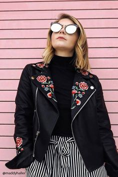 A faux leather moto jacket featuring floral embroidery, asymmetrical zip-up front, notched collar with snap-buttons, two front zippered pockets, buckle accents at the hem, and long zippered sleeves.