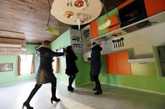 Pessoas visitam a cozinha da casa de cabeça para baixo (Foto: Reuters/Ilya Naymushin)