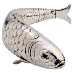 Hallmarked silver box in the form of an articulated fish with gemstone set red eyes. Hinged head and mouth open to hold trinkets or spices. ...