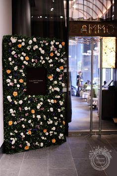 Each wall is over 7 feet tall with a background of fresh foliage and flowers including Bombastic spray rose, white lisianthus and sweet william, orange Voodoo rose, pink bouvardia and purple statice.