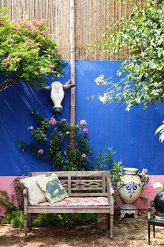 Isabelle Tuchband's colorful boho garden via The Selby ...blue, pink, wood bench, carved cow skull