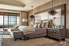 Set against an Innovations wallcovering with a wood-like appearance, the custom headboard and upholstered bed anchor the master bedroom. Arteriors pendants, above Noir bedside tables, and a Palecek floor lamp provide eye-catching lighting elements.