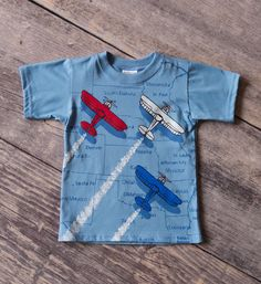 Zoom to the airshow with this patriotic airplane shirt for little boys!  A baby blue shirt with map graphic is overlaid with a trio of soaring red, white and blue airplanes.  This boys 4th of July t-shirt features rib knit collar and classic boys patriotic style.