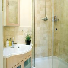 Small Ensuite Shower Room. Decent sized sink with storage underneath.  Curved shower door.