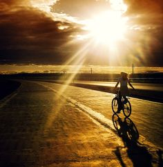 a road, a bike, sun and clouds