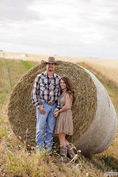 Nebraska country farm engagement session with hay bales. ©trinjensenphotography #cowboyboots #cowboyhat #haybales #farm #plaid #naturallight