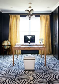 this clean and classic office space has all the right elements for high style... black walls + zebra rugs + yellow panels + standing globe + studded ottoman as chair =domestic bliss(photographed by werner straube for traditional homes) via dustattic jacket