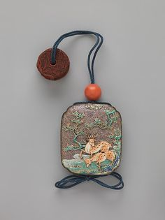 Case (Inrô) with Design of Deer and Maple Trees (obverse); Mount Fuji (reverse) Period: Edo period (1615–1868) Date: ca. 1820 Culture: Japan Medium: Case: lacquer with pottery plaques; Fastener (ojime): coral; Toggle (netsuke): red lacquer carved with design of Chinese figure and plant