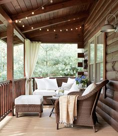 Light and Airy: String lights from Target twinkle over the front porch of this Ohio lake house, and Pottery Barn wicker furniture surrounds an antique folding table, where the family plays cards. Click through for more porches and patios we love. Outdoor Spaces, Outdoor Living, Outdoor Decor, Outdoor Seating, Outdoor Patios, Outdoor Kitchens, Extra Seating, Building A Porch, House With Porch