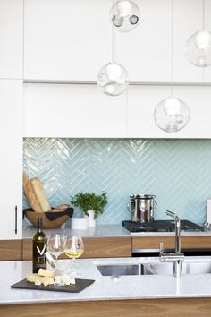 Interior Design by Falken Reynolds - Vancouver loft kitchen and deck with American Mid Century Modern inspired walnut cabinets, Caesarstone counters, aqua herringbone glass tile backsplash, oak hardwood floors, Bocci28 pendant, photo by Ema Peter
