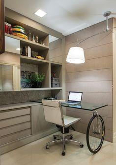 A roda de bicicleta utilizada como base da mesa de trabalho faz alusão ao esporte praticado pelo cliente. A bancada foi integrada à estante projetada especialmente para o espaço, utilizado como home office e biblioteca.