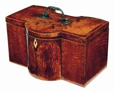 A George III satinwood barrel front tea caddy, with an inverted bow back having tulipwood cross banding and stringing, the hinged cover with a foliage marquetry spray and a cast brass handle revealing a pair of oval hinged lidded canisters flanking a later treen bowl with spoon and tong apertures behind. 6.25in (16cm) h, 11.25in (28.5cm) w. Lid warped and sides bowed.  Woolley & Wallis