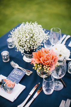 Navy table cloth with three vases: baby's breath, white hydrangeas mixed with coral roses, and a single white or coral peony.
