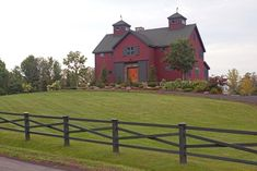 Yankee Barn Home with sliding barn doors over front door - fantastic cupolas and cross board fence