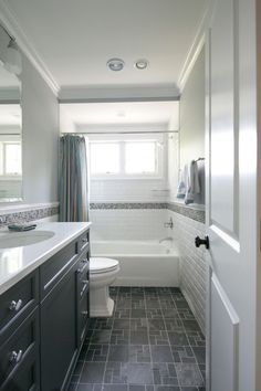 Dark slate floor, dark espresso vanity, light counter top, greyish accent tile, white/grey tile on walls and shower, and grey on tops of walls