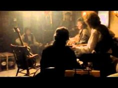 Traveling Wilburys End Of The Line   L–R: Roy Jeff Lynne, Bob Dylan, George Harrison, and Tom Petty. Roy Orbison is represented here by his guitar on a chair as he died before this video was finished.