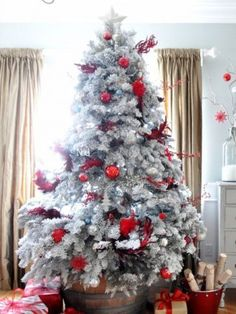 I love the idea of a flocked Christmas tree in a rustic bucket. The red ornaments make it pop!