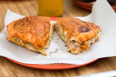 Pambazo is a Mexican sandwich made with bread soaked in guaijllo sauce and filled with papas con chorizo.