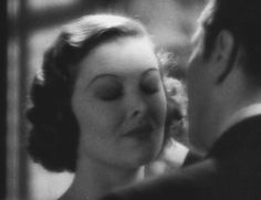 Myrna Loy is flustered after a kiss from Warner Baxter in Penthouse (1933).