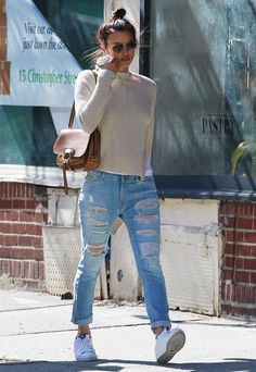 Irina Shayk runs errands in distressed jeans, a tan sweater, and sneakers. She topped off the outfit with a messy bun and a tan shoulder bag.