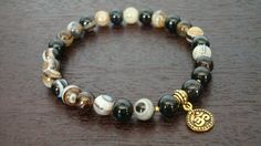 """mens sardonyx strength mala bracelet, made with high quality sardonyx and gold or silver om charm. sardonyx is a beautiful stone made of banded onyx, and is a stone of protection and strength. it stimulates our driving for, as well as our understanding of, a meaningful existence. this stone encourages stability, self-confidence, attracts friends and has been used to help lift depression. it is believed to help generate a more positive attitude, bring happiness to marriage and to """"live-in""""…"""