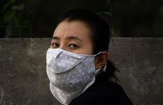A woman wears a face mask as she walks along a main road in Beijing June 4, 2012. REUTERS/David Gray