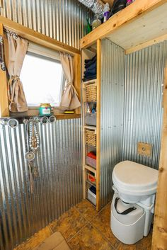 Good storage in this tiny bathroom - corrugated metal walls, composting toilet