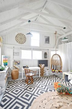 Stylish She Sheds: Modern coastal shed interior with tropical rattan accents and hanging swing chair | NONAGON.style #backyardshed
