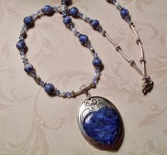 In this lovely one of a kind pendant necklace, I attached a sodalite puff heart to a silvertone pendant and then wrapped it with silver wire to