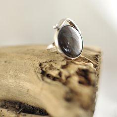 """Een hele fijne edelsteen om met je kleding te combineren; er zit o.a. bruin in de steen en zwart. De ring is van het type """"Swing', er zit een zilveren art-deco achtige versiering aan gesoldeerd. De bruin zwarte edelsteen werd vroeger al veel door krijgers gebruikt. Tijgerijzer scherpt het verstand en versterkt je moed."""
