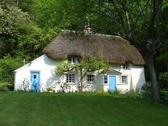 Loving blue doors and the thatched roof,  a sweet cottage to call home.