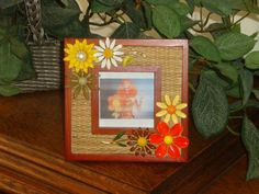 Hippie era enamelled metal flower pins adorn a wood frame with a woven mat. Frame is 5 3/4 inches square and holds your favorite 2 1/2 inch square