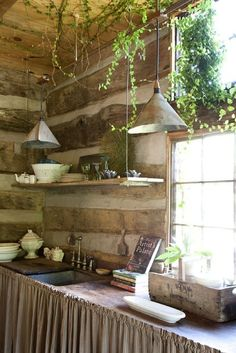[CasaGiardino]  Square log construction with tin pendents and butcher block counter.  Farm style faucets.  Ivy takes over the ceiling and gives it a greenhouse effect.
