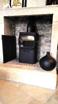 Poêle à bois Jotul F105 noir mat installé dans une ancienne cheminée.…