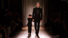 A new collection for men and children captured at a runway show while the little boy cries from his nervousness.