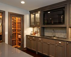 Wet Bar With Glass Cabinets And TV