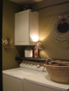 Small Laundry ideas. Shelf and cabinets above washer and dryer with curtain rod for hang dry space!