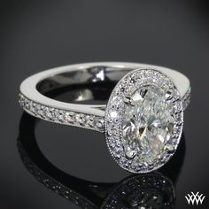 This beautiful custom design incorporates a half eternity shank and a cathedral bead set halo with milgrain edging. The 1.58ct Oval Cut Diamond is held securely with 4 clawed prongs. -
