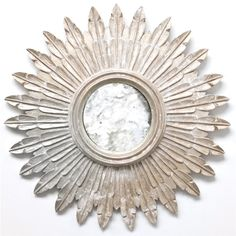 """This 24"""" mirror has rays in the shape of leaves. Hand-carved wood finished in silver leaf."""