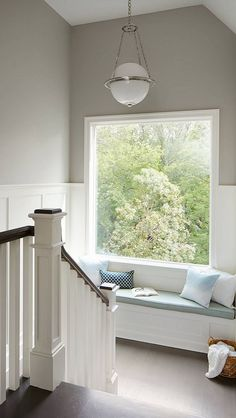 Beautiful landing with white rails, a built-in window seat, a large picture window and walls painted in Sherwin Williams Mindful Gray | Summit Signature Homes, Inc Stairways, ideas, stair, home, house, decoration, decor, indoor, outdoor, staircase, stears, staiwell, railing, floors, apartment, loft, studio, interior, entryway, entry.